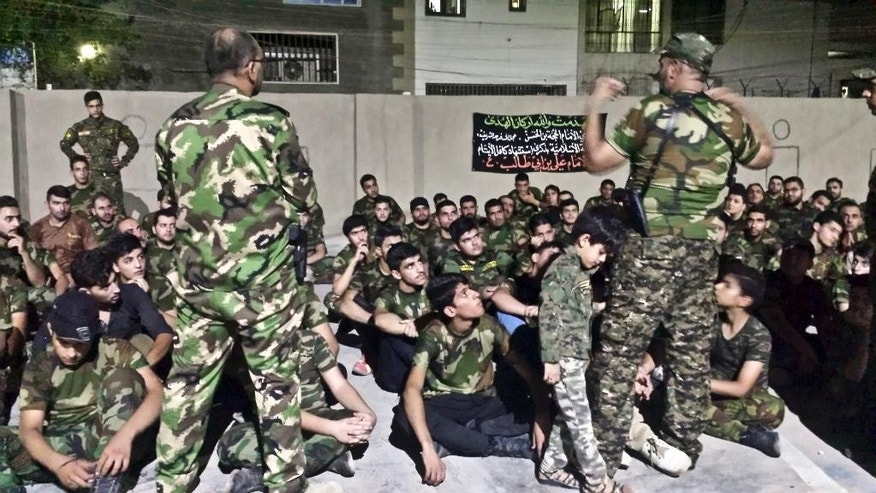 In this Tuesday, July 14, 2015 photo, Iraqi volunteers with Popular Mobilization Forces train in Baghdad, Iraq. The Associated Press has found that militia forces battling the Islamic State group are actively training children under 18 years old. (AP Photo/Vivian Salama)