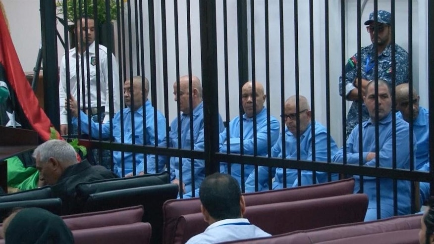 In this image made from AP video, former Libyan officials who served during Moammar Gadhafi's era sit in the defendants' cage during their trial for crimes committed during Libya's 2011 uprising in a courtroom in Tripoli, Libya, Tuesday, July 28, 2015. The court sentenced Gadhafi's son, Seif al-Islam Gadhafi, who was not present inside the courtroom, to death by firing squad after convicting him of murder and inciting genocide during the 2011 civil war. (AP Photo via AP video)