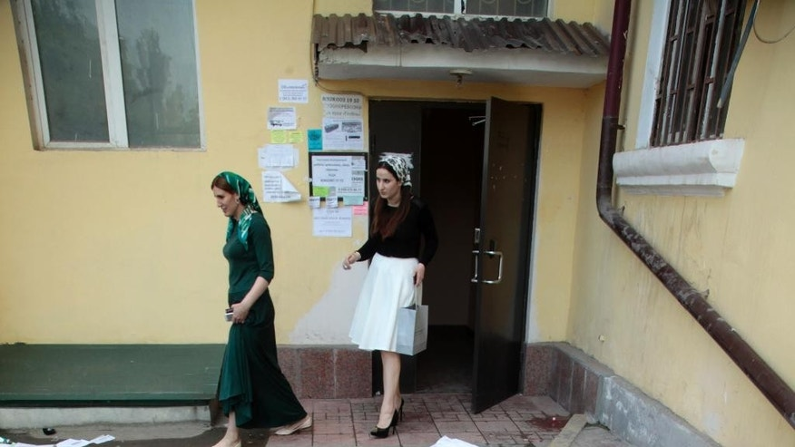 FILE - In this photo taken on Wednesday, June 3, 2015, women leave an apartment building, where a human rights group office is situated, in Grozny, Russia, Wednesday, June 3, 2015. Masked men broke into the office of the Committee against Torture in the regional Chechen capital of Grozny on Wednesday, smashing furniture and sending the occupants fleeing through the windows, their colleagues said. (AP Photo/Musa Sadulayev, file).