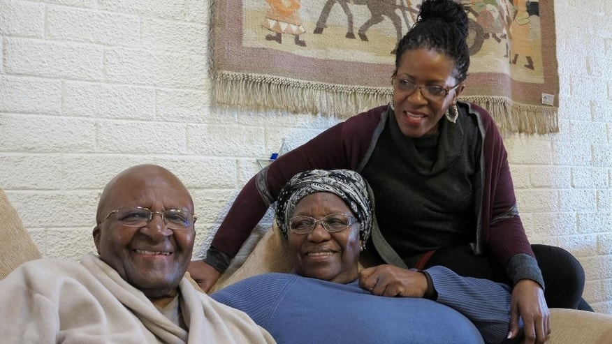 FILE - This Tuesday, July 21, 2015 photo provided by Oryx Media shows retired Anglican Archbishop Desmond Tutu, left, with his wife, Leah, center, and daughter, Mpho, at their home in Cape Town, South Africa. On Tuesday, July 28, 2015 his foundation said he returned for hospital treatment, a week after he left a hospital following an intensive antibiotics course for an infection. (Benny Gool/Oryx Media via AP)