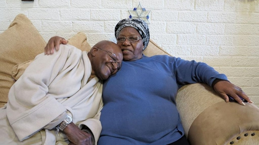 FILE - This Tuesday, July 21, 2015 photo provided by Oryx Media shows retired Anglican Archbishop Desmond Tutu, left, with his wife Leah at their home in Cape Town, South Africa. On Tuesday, July 28, 2015 his foundation said he returned for hospital treatment, a week after he left a hospital following an intensive antibiotics course for an infection. (Benny Gool/Oryx Media via AP)