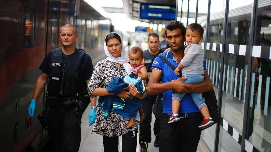 German federal police officers escort a Afghan family after they arrived the main station in Rosenheim, Germany, Tuesday, July 28, 2015. Thousands of refugees arrived in the border region between Austria and Germany in the last few weeks.  (AP Photo/Matthias Schrader)