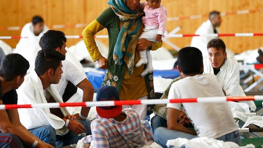Refugees wait for their first registration at a facility of the German federal police after they were picked up in Rosenheim, Germany, Tuesday, July 28, 2015. Thousands of refugees arrived in the border region between Austria and Germany in the last few weeks. (AP Photo/Matthias Schrader)