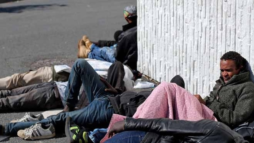 Migrants wait near a motorway leading to the ferry port to cross the English channel, in Calais, northern France.