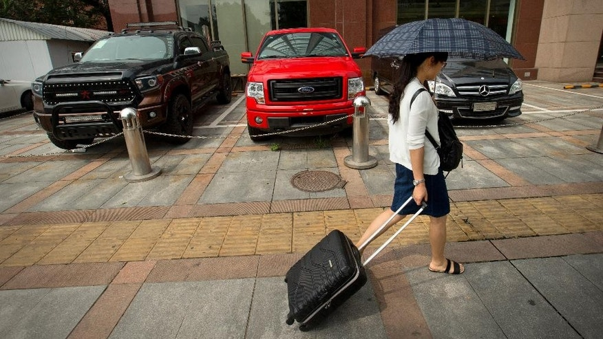 In this Tuesday, July 28, 2015 photo, a woman walks past vehicles parked outside of a luxury import car dealership in Beijing. June sales in the biggest car market by number of vehicles sold shrank by 3.4 percent from a year earlier as an economic slowdown deepened and smog-choked cities tried to curb growth in car ownership. Sales growth has steadily declined from 2009's explosive peak of 45 percent but the latest figures surprised analysts who were forecasting a healthy 7 to 8 percent for this year. (AP Photo/Mark Schiefelbein)
