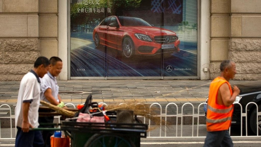 In this Tuesday, July 28, 2015 photo, maintenance workers walk past a billboard for a Mercedes sedan outside a car dealership in Beijing. June sales in the biggest car market by number of vehicles sold shrank by 3.4 percent from a year earlier as an economic slowdown deepened and smog-choked cities tried to curb growth in car ownership. (AP Photo/Mark Schiefelbein)
