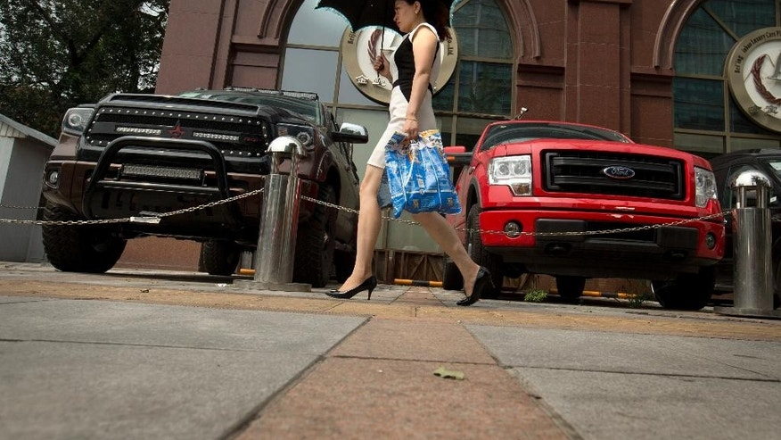 In this Tuesday, July 28, 2015 photo, a woman walks past pickup trucks parked outside a luxury import car dealership in Beijing. General Motors Co.'s $5 billion initiative to create cars for China and other emerging markets comes just as automakers face a collapse in the booming Chinese demand they were counting on to power their growth. June sales in the biggest car market by number of vehicles sold shrank by 3.4 percent from a year earlier as an economic slowdown deepened and smog-choked cities tried to curb growth in car ownership.  (AP Photo/Mark Schiefelbein)