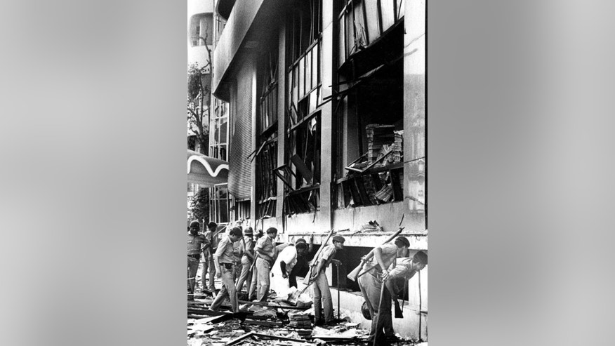 FILE- In this March 12, 1993 file photo, Indian paramilitary officers search for survivors, after a massive explosion ripped through the Bombay Stock Exchange in Mumbai, India. Yakub Abdul Razak Memon, an accountant, convicted of providing financial and logistical support in the series of bombings that shook India's business and entertainment hub in 1993 is scheduled to be hanged Thursday, July 30, 2015. About 300 prominent citizens, including at least eight retired judges of the Supreme Court and the Delhi High Court, have urged India's president to commute Memon's sentence to life in prison, reflecting what appears to be growing uneasiness in India with the death penalty. (AP Photo/Sherwin Crasto, file)