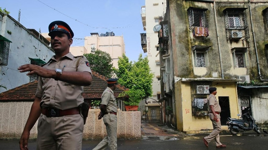 Indian policemen stand guard in front of the building where Yakub Abdul Razak Memon's family resides in Mumbai, India, Thursday, July 30, 2015. Memon, 53, the only death row convict in India's deadliest terror attack, the 1993 Mumbai bombings that killed 257 people, was hanged early Thursday after the country's president rejected a last-minute mercy plea, several newspapers and TV stations reported. He was executed inside a prison in western India where he had been incarcerated since 1994. (AP Photo/Rafiq Maqbool)
