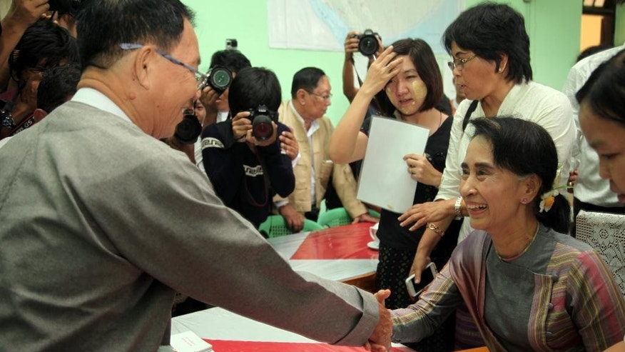 Myanmar opposition leader Aung San Suu Kyi, right, submits her documents for the upcoming general election at an election commision office, Wednesday, July 29, 2015, in outskirts of Yangon, Myanmar. Myanmar's democracy leader Aung San Suu Kyi on Wednesday registered for November elections to keep her seat in parliament and challenge the ruling military-backed party. (AP Photo/Khin Maung Win)