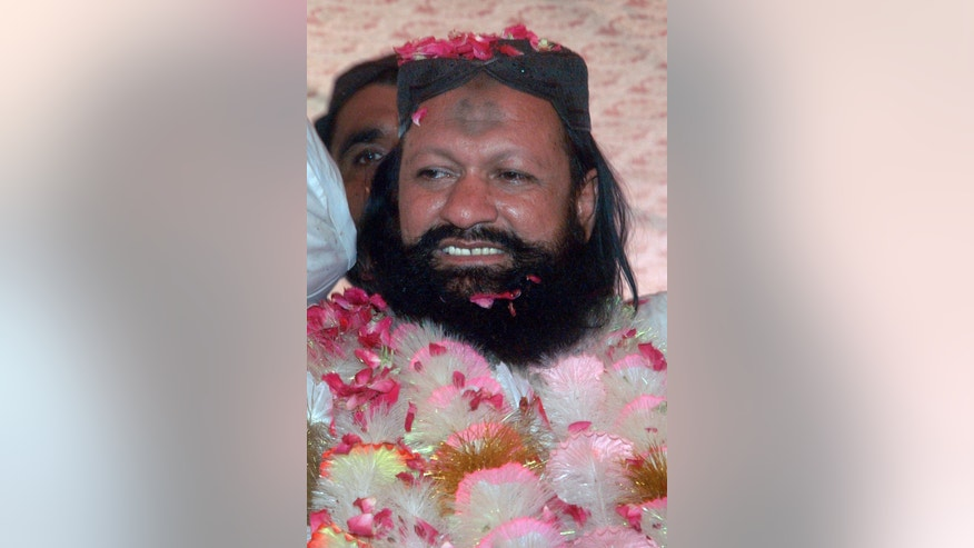 FILE - In this July 15, 2011, file photo, Malik Ishaq, a leader of the banned Sunni Muslim group Lashkar-e-Jhangvi, is greeted by supporters with rose-petals upon his arrival at his hometown in Rahim Yar Khan, Pakistan, after his release from jail. Pakistani police gunned down Ishaq, one of the country's most-feared Sunni militant leaders, and 13 followers in a mysterious pre-dawn shootout Wednesday, July 29, 2015, killing a man believed to behind the slaughter of hundreds of the nation's minority Shiites. (AP Photo/Khalid Tanveer, File)