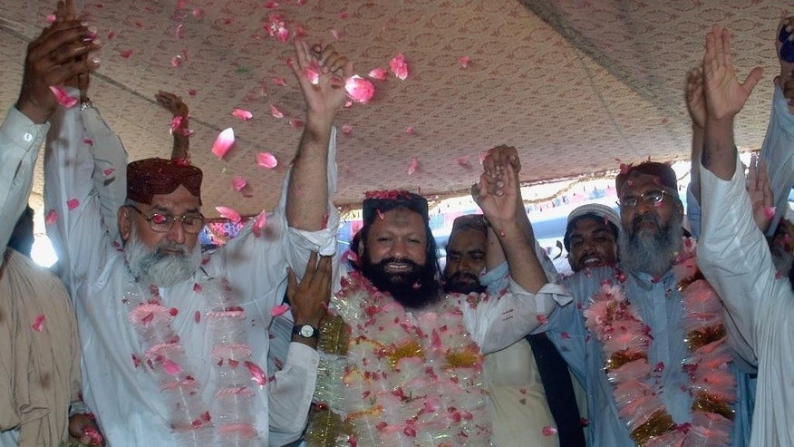 FILE - In this July 15, 2011, file photo, Malik Ishaq, center, a leader of the banned Sunni Muslim group Lashkar-e-Jhangvi, and his colleagues, raise hands in response their supporters who greeted him with rose-petals upon his arrival at his hometown in Rahim Yar Khan, Pakistan, after his release from jail. Pakistani police gunned down Ishaq, one of the country's most-feared Sunni militant leaders, and 13 followers in a mysterious pre-dawn shootout Wednesday, July 29, 2015, killing a man believed to behind the slaughter of hundreds of the nation's minority Shiites. (AP Photo/Khalid Tanveer, File)