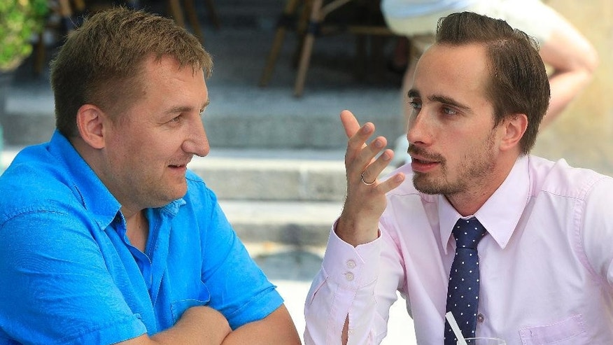 In this July 24, 2015 photo, Radek Ciszewski, left, and Marek Bogacki, discuss how far Poland has come since throwing off communism 26 years ago, in Warsaw, Poland. Ciszewki, a consultant, and Bogacki, a director at an insurance company, are among the Poles are doing well thanks to a quarter century of constant economic growth. However, there are still many Poles who remain trapped in low wages and insecure job conditions, creating social frustration that has come to the surface in a year of political elections. (AP Photo/Czarek Sokolowski)