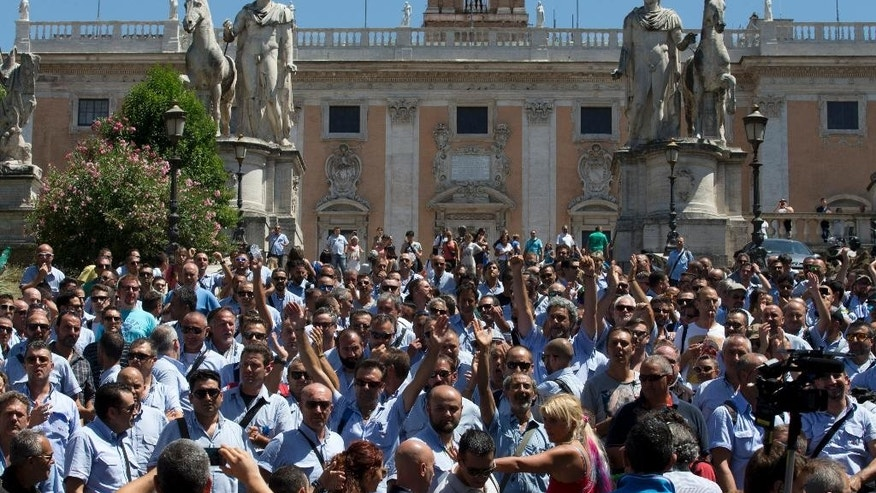 Public transport workers raise their hands during a protest at Campidoglio Capitol Hill square in Rome, Wednesday, July 29, 2015. Just when Rome needs to be at its best, the city is being shamed by corruption scandals and a breakdown in public services — especially in the mass transit that many of the pilgrim masses will be using. (AP Photo/Alessandra Tarantino)