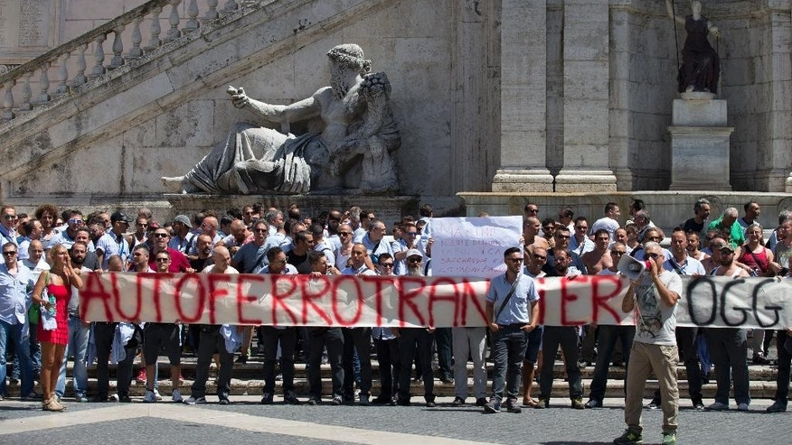 Public transport workers hold a banner reading in Italian ' Transport workers united and proud today more than yesterday ' during a protest at Campidoglio Capitol Hill square in Rome, Wednesday, July 29, 2015. Just when Rome needs to be at its best, the city is being shamed by corruption scandals and a breakdown in public services — especially in the mass transit that many of the pilgrim masses will be using. (AP Photo/Alessandra Tarantino)