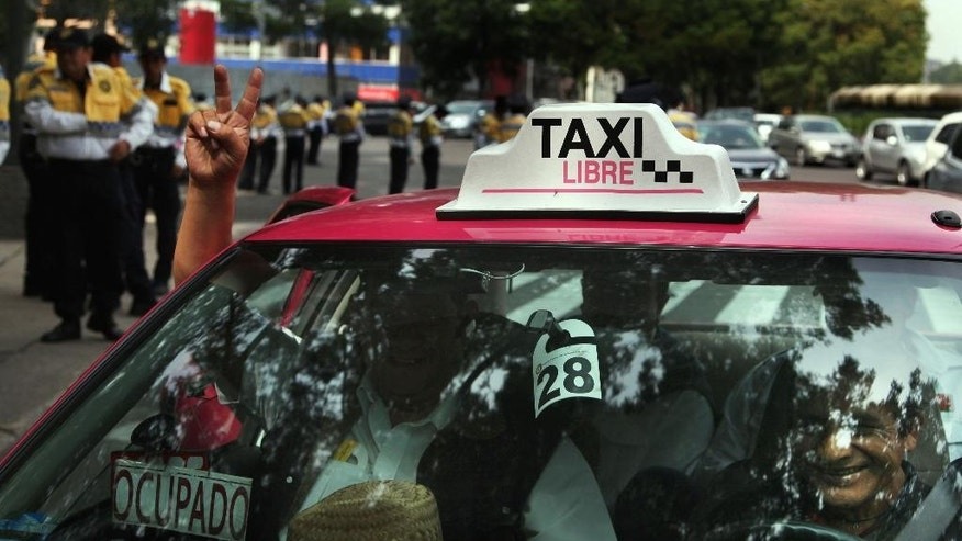 Street taxi drivers protest against the smartphone-based ride service Uber, in Mexico City, Wednesday, July 29, 2015. The Mexican taxi drivers' union called for a protest against unlicensed and Uber taxis working in the city. However Uber is increasingly popular among middle- and upper-class Mexicans, as they turn to what is seen as a safer, more reliable, more pleasant and cost-competitive alternative to street cabs. (AP Photo/Marco Ugarte)
