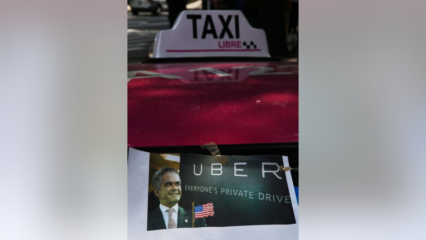 A poster of Mexico City Mayor Miguel Angel Mancera portraying him as a sellout, is seen taped to the windshield of a street taxi during a protest against the smartphone-based ride service Uber, in Mexico City, Wednesday, July 29, 2015. The Mexican taxi drivers' union called for a protest against unlicensed and Uber taxis working in the city. However Uber is increasingly popular among middle- and upper-class Mexicans, as they turn to what is seen as a safer, more reliable, more pleasant and cost-competitive alternative to street cabs. (AP Photo/Marco Ugarte)