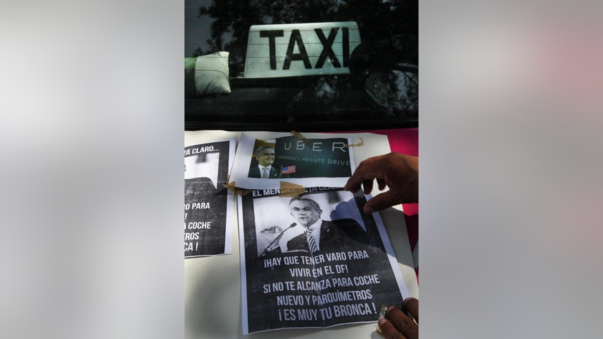 "Posters of Mexico City Mayor Miguel Angel Mancera portraying him as a sellout, are taped to the hood of a street taxi during a protest against the smartphone-based ride service Uber, in Mexico City, Wednesday, July 29, 2015. The Mexican taxi drivers' union called for a protest against unlicensed and UBER taxis working in the city. However Uber is increasingly popular among middle- and upper-class Mexicans, as they turn to what is seen as a safer, more reliable, more pleasant and cost-competitive alternative to street cabs. The message on the poster reads in Spanish; ""You need to have money to live in Mexico City! If you do not have enough for a new car and parking fees, that's your problem!"" (AP Photo/Marco Ugarte)"