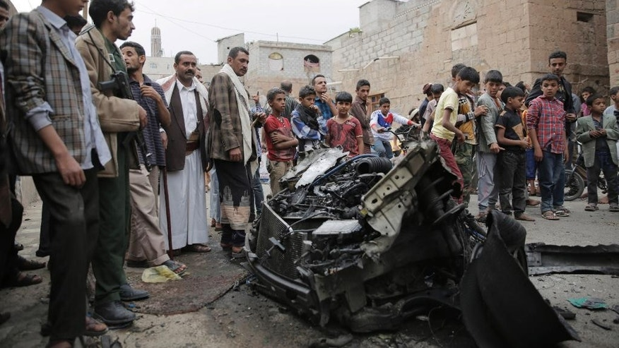 People stand amid wreckage of a vehicle at the site of a car bomb attack next to a Shiite mosque in Sanaa, Yemen, Wednesday, July 29, 2015. The car bomb exploded in Sanaa, next to the mosque belonging to the minority al-Bohra community, a Shiite sect, killing a few people and wounding several, Yemen's rebel-held Interior Ministry said in a statement. (AP Photo/Hani Mohammed)