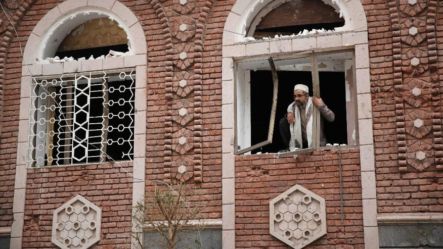 A man stands behind a damaged window at the site of a car bomb attack next to a Shiite mosque in Sanaa, Yemen, Wednesday, July 29, 2015. The car bomb exploded in Sanaa, next to the mosque belonging to the minority al-Bohra community, a Shiite sect, killing a few people and wounding several, Yemen's rebel-held Interior Ministry said in a statement. (AP Photo/Hani Mohammed)