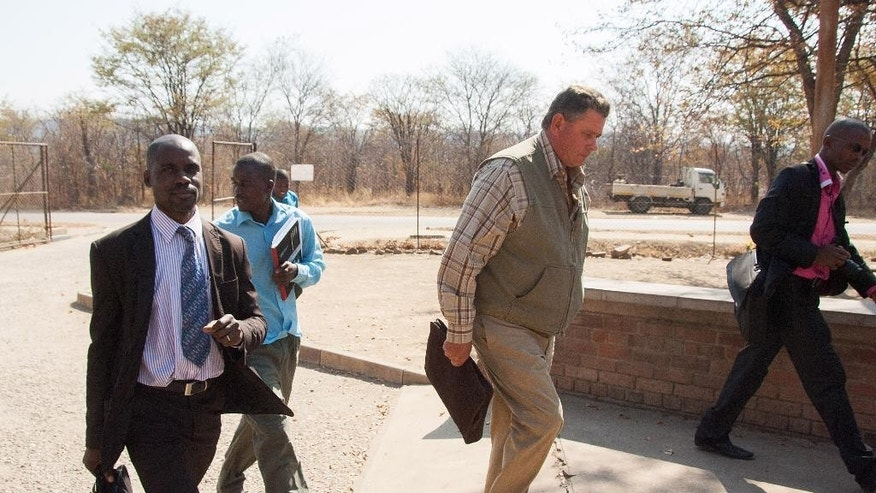 Theodro Bronkhorst, centre, a professional hunter, arrives for his appearance at the magistrates courts in Hwange about 700 kilometres south west of Harare, Wednesday, July 29, 2015. Bronkhorst who was granted $1000 bail has been charged with  failure to prevent an unlawful hunt that resulted in the killing of Cecil the lion by Minnesota dentist, Walter James Palmer, in Zimbabwe.  (AP Photo)