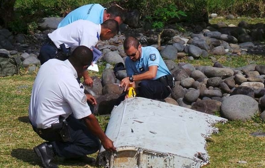 July 29: French gendarmes and police inspect a large piece of plane debris which was found on the beach in Saint-Andre, on the French Indian Ocean island of La Reunion.