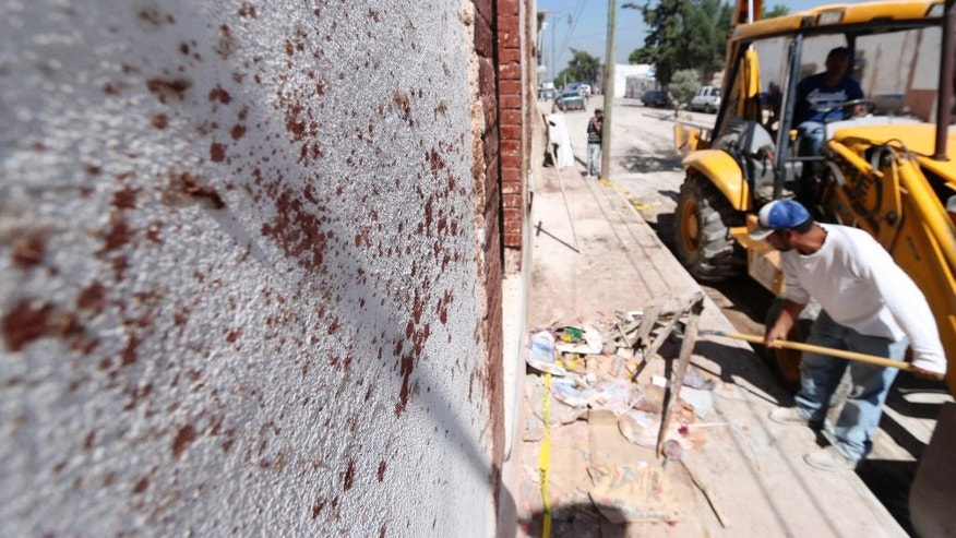 Workers collect debris next to a blood-stained wall, on the site where a truck slammed into a a religious procession in the town of Mazapil, Mexico, Thursday July 30, 2015. Dozens were killed and hundreds injured after the truck, which officials said was loaded with building materials, apparently lost its brakes and ran into the crowd that was celebrating the festival of its patron, Jesus Nazareno, with a procession to the church. (AP Photo)