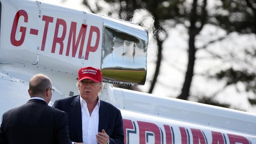 Presidential contender Donald Trump, speaks with an unidentified person after he arrived by helicopter during the 1st first day of the Women's British Open golf championship on the Turnberry golf course in Turnberry, Scotland, Thursday, July 30, 2015. (AP Photo/Scott Heppell)