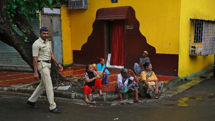 An Indian police officer stops a family at a barricade in the neighborhood of Yakub Abdul Razak Memon's family residence in Mumbai, India, Thursday, July 30, 2015. Memon, 53, the only death row convict in India's deadliest terror attack, the 1993 Mumbai bombings that killed 257 people, was hanged early Thursday after the country's president rejected a last-minute mercy plea, several newspapers and TV stations reported. He was executed inside a prison in western India where he had been incarcerated since 1994. (AP Photo/Rafiq Maqbool)