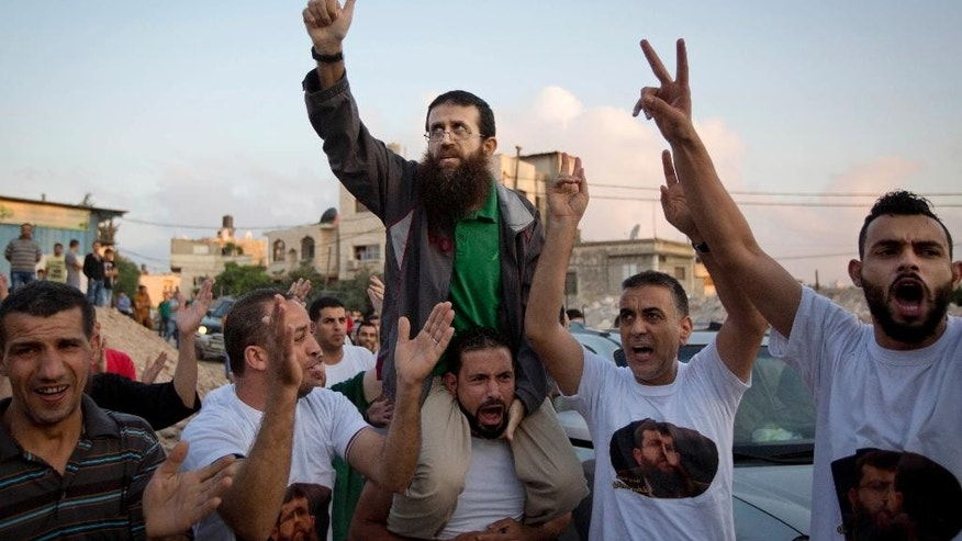 FILE - In this Sunday, July 12, 2015, file photo, Palestinian Khader Adnan, center, who recently ended a 55-day hunger strike, is greeted by Palestinians after his release from an Israeli prison in the West Bank village of Arrabeh near Jenin. Israel's parliament passed a contentious law on Thursday that would permit the force-feeding of inmates on hunger strike, eliciting harsh criticism over the practice. (AP Photo/Majdi Mohammed, File)