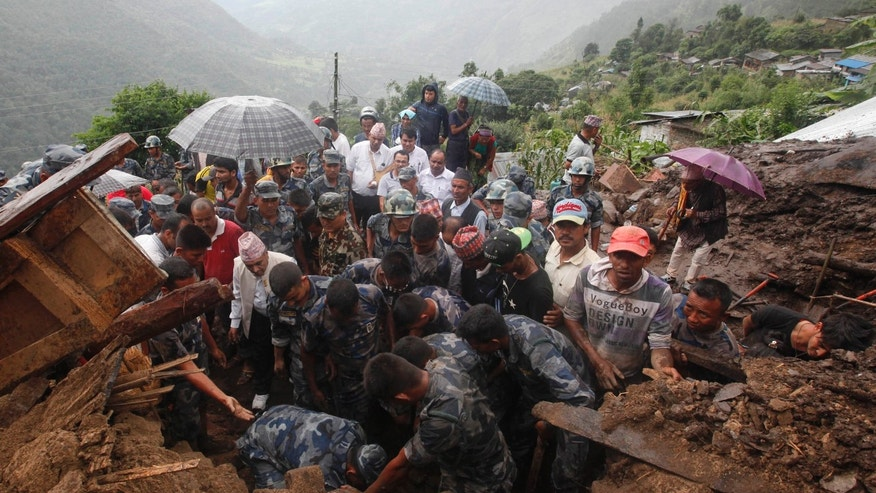 Thursday, July 30, 2015: Nepalese policemen search for bodies of victims from the debris after a landslide in Lumle village, about 200 kilometers (125 miles) west of Kathmandu, Nepal.