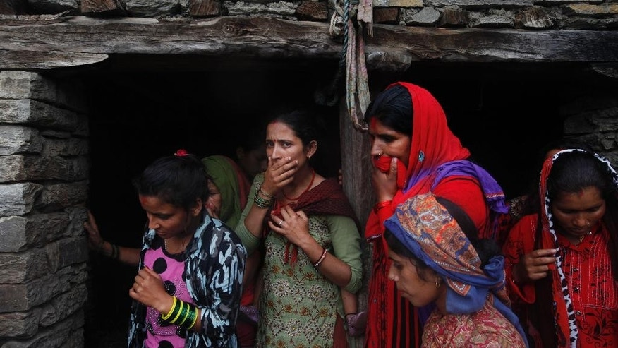Nepalese women react after rescuers recovered a dead body of a victim from the debris after a landslide in Lumle village, about 200 kilometers (125 miles) west of Kathmandu, Nepal, Thursday, July 30, 2015. Landslides in a mountain area of Nepal buried three villages Thursday, killing several people, authorities said.(AP Photo/Niranjan Shrestha)