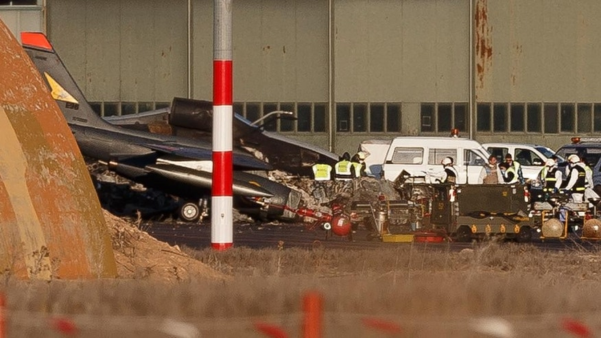 FILE - A Tuesday, Jan. 27, 2015 file photo showing investigators working around the wreckage of planes the day after a Greek F-16 jet crashed at Albacete airbase, Spain. Loose papers left in the cockpit of an F-16 that crashed at a Spanish airbase could have sent the fighter jet into its deadly spiral, French investigators have concluded. The report released this week brings an end to a multinational investigation into what happened before the Greek plane's failed takeoff and crash.  (AP Photo/Daniel Ochoa de Olza)