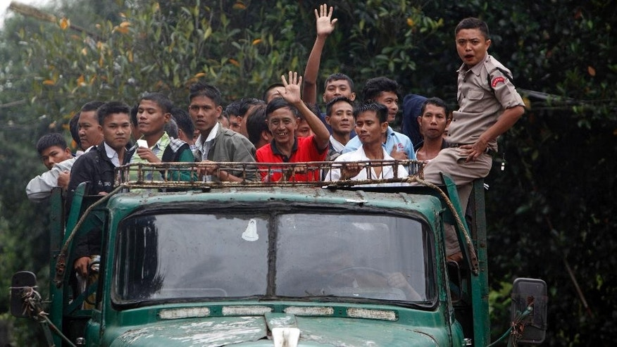 Released prisoners on a police truck wave to their relatives and colleagues at entrance of Insein Prison, Thursday, July 30, 2015, in Yangon. Nearly 7,000 prisoners in Myanmar, including some former military intelligence officials who had been purged by their army colleagues, have been given presidential pardons. (AP Photo/Khin Maung Win)