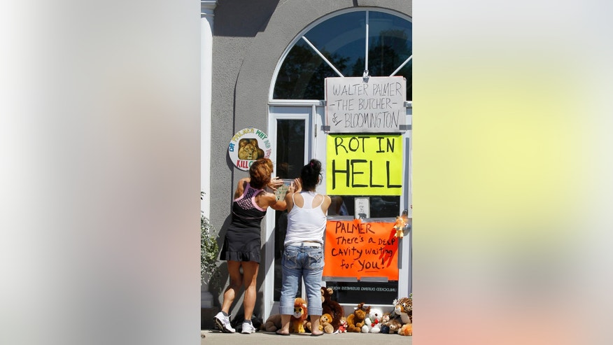 Women add signs to the door outside Dr. Walter James Palmer's dental office in Bloomington, Minn., Wednesday, July 29, 2015. Palmer reportedly paid $50,000 to track and kill a black-maned lion, just outside Hwange National Park in Zimbabwe. (AP Photo/Ann Heisenfelt)
