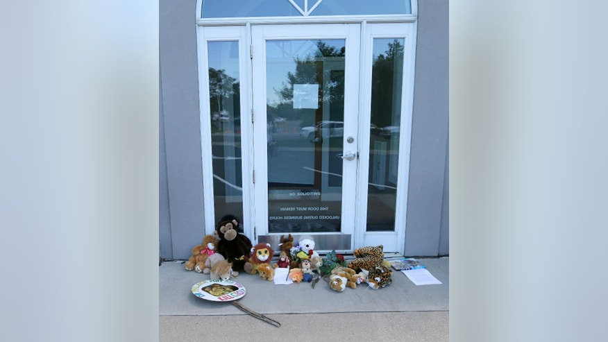 Stuffed animals and notes lie outside Dr. Walter James Palmer's dental office in Bloomington, Minn., Wednesday, July 29, 2015. Authorities allege that Palmer paid $50,000 to track and kill Cecil, a protected lion, just outside Hwange National Park in Zimbabwe. (AP Photo/Ann Heisenfelt)