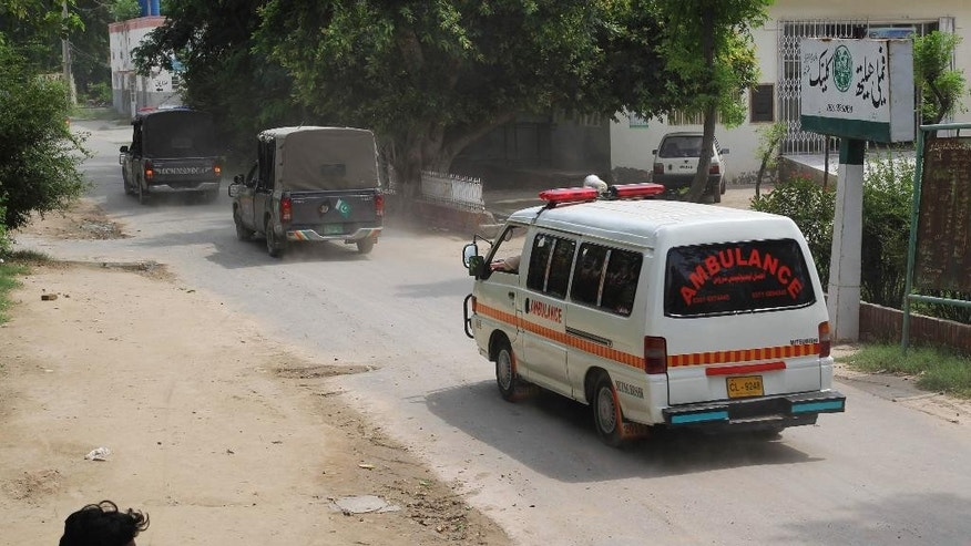 Police vehicles escort an ambulance carrying the dead bodies of Sunni militant leader Malik Ishaq and others to their hometown, in Muzaffargarh, Pakistan, Wednesday, July 29, 2015. Ishaq, one of Pakistan's most-feared Islamic militant leaders, believed to be behind the killing of scores of minority Shiites, was gunned down along with 13 associates during a militant assault on a police convoy that was transporting him from prison on Wednesday. (AP Photo/Asim Tanveer)