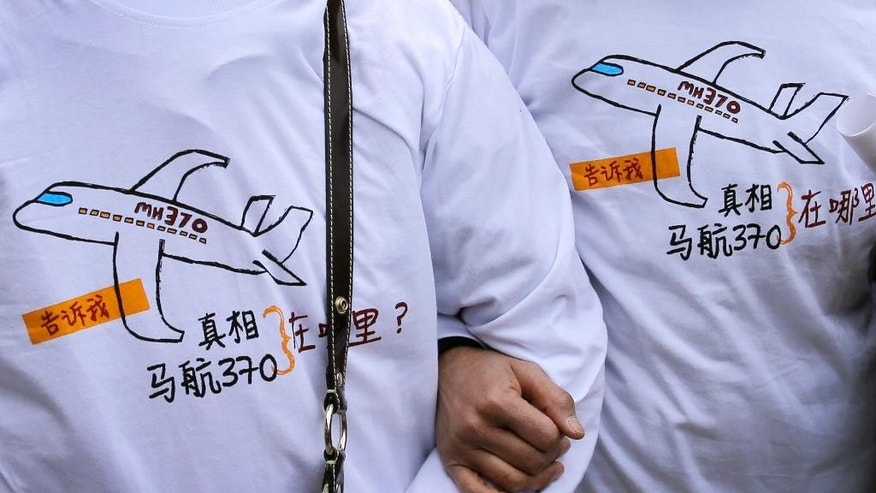 "FILE - In this March 8, 2015 file photo, relatives of passengers on board the Malaysia Airlines Flight 370 that went missing on March 8, 2014, wear T-shirts carrying a message for the missing flight as they leave Yonghegong Lama Temple after a gathering of family members of the missing passengers, in Beijing. The T-shirt reads: ""Tell me the truth, where is MH370?"" A piece of aircraft wing found on an island in the western Indian Ocean is unlikely to alter the seabed search for a missing Malaysia Airlines jetliner in the southern Indian Ocean, the search leader said Thursday, July 30, 2015. (AP Photo/Andy Wong, File)"