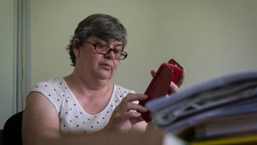 Jacquita Gomes, 53, checks her mobile phone at her office in Kuala Lumpur, Malaysia on Thursday, July 30, 2015.  Gomes is torn about whether to believe that plane debris found more than 16 months after the mysterious disappearance of Malaysia Airlines Flight 370 is the first concrete evidence that her husband is truly gone. (AP Photo/Joshua Paul)