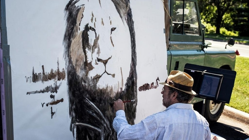 Artist Mark Balma paints a mural of Cecil, a well-known lion killed by Minnesota dentist Walter Palmer during a guided bow hunting trip in Zimbabwe, as part of a silent protest outside Palmer's office in Bloomington, Minn., Wednesday, July 29, 2015. Palmer said that he had no idea the lion he killed was protected and that he relied on the expertise of his local guides to ensure the hunt was legal. (Glen Stubbe/Star Tribune via AP) MANDATORY CREDIT