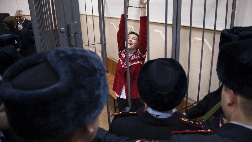 FILE - In this Wednesday, March 4, 2015 file photo, Ukrainian jailed military officer Nadezhda Savchenko, center, reacts as she listens to the court's decision in a cage at a court room in Moscow, Russia. A preliminary hearing in the trial of military pilot Nadezhda Savchenko charged in the deaths of two Russian journalists has started Thursday, July 30, 2015, in Russia's southern town of Donetsk. (AP Photo/Ivan Sekretarev, File)