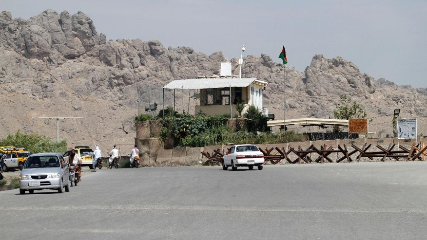 Afghans travel by motorbike and car in front of Mullah Mohammad Omar's house, in Kandahar province, south of Kabul, Afghanistan, Friday, July 31, 2015. The Taliban confirmed the death of longtime leader Mullah Omar and appointed his successor Thursday, as a new round of peace talks was indefinitely postponed amid concerns over how committed the new leadership is to ending the militant group's 14-year insurgency. (AP Photo/Allauddin Khan)