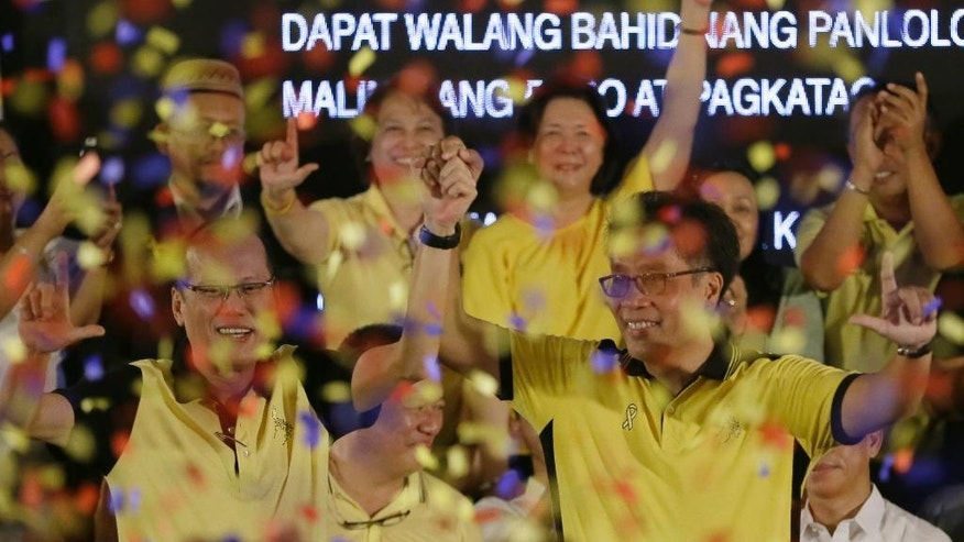 "Confetti rain on Philippine President Benigno Aquino III, left, and Interior Secretary Manuel ""Mar"" Roxas II as Aquino endorses Roxas as the administration's standard bearer for the May 2016 presidential elections, Friday, July 31, 2015 at the historic Club Filipino in suburban San Juan, east of Manila, Philippines. The 58-year-old former congressman and senator said he was honored to be endorsed by Aquino of the dominant Liberal Party. (AP Photo/Bullit Marquez)"