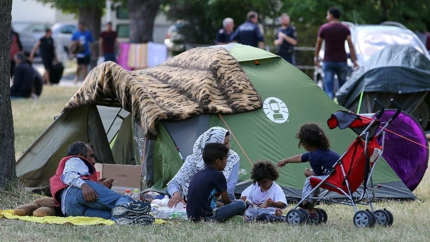 Refugees wait outside the refugee camp in Traiskirchen, Austria, Friday, July 31, 2015. Austria's federal government plans to change the constitution in attempts to end a standoff with provincial leaders over finding housing for a massive influx of migrants. The plan, announced Friday, would allow the federal government to provide shelter for migrants seeking asylum anywhere in Austria on and in property owned by the government. (AP Photo/Ronald Zak)