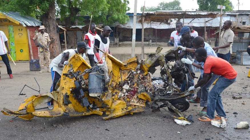 People inspect a damaged tricycle at the site of a bomb explosion in Maiduguri, Nigeria, Friday, July 31, 2015 . A woman suicide bomber killed many people at a crowded market early Friday in a blast that thundered across the northeastern Nigerian city of Maiduguri, witnesses said. (AP Photo/Jossy Ola)