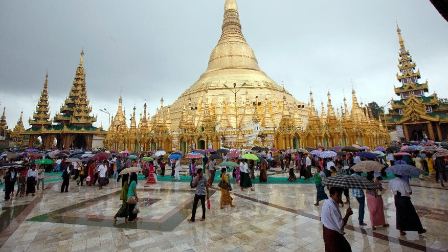 Buddhist devotees hold umbrellas as they visit Myanmar's famous Shwedagon Pagoda in the rain during the full moon day of Waso, the fourth month of Myanmar calendar and the beginning of Buddhist Lent, Friday, July 31, 2015, in Yangon, Myanmar. (AP Photo/Khin Maung Win)