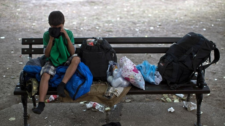 A boy from Syria sits on a bench in a park in Kanjiza, close to the Serbian border with Hungary, Serbia, Friday, July 31, 2015. Hungary's foreign minister said Friday that over 100,000 illegal migrants have reached the country so far this year, nearly all of them entering through its southern border with Serbia. (AP Photo/Marko Drobnjakovic)