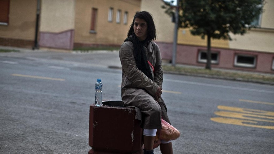 A migrant from Syria rests after receiving a food package in Kanjiza, close to the Serbian border with Hungary, Serbia, Friday, July 31, 2015. Hungary's foreign minister said Friday that over 100,000 illegal migrants have reached the country so far this year, nearly all of them entering through its southern border with Serbia. (AP Photo/Marko Drobnjakovic)