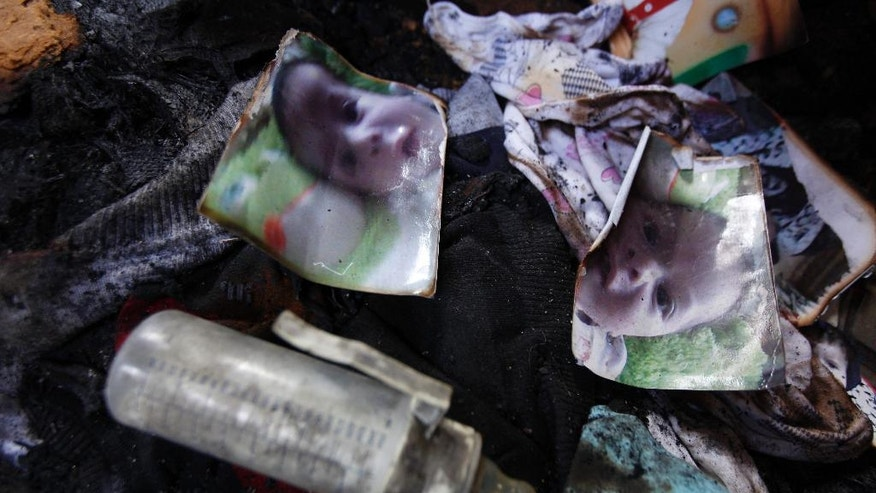 Photos of a one-and-a-half year old boy, Ali Dawabsheh, lie  in a house that had been torched in a suspected attack by Jewish settlers  in Duma village near the West Bank city of Nablus, Friday, July 31, 2015. The boy died in the fire, his four-year-old brother and parents were wounded, according to a Palestinian official from the Nablus area. (AP Photo/Majdi Mohammed)
