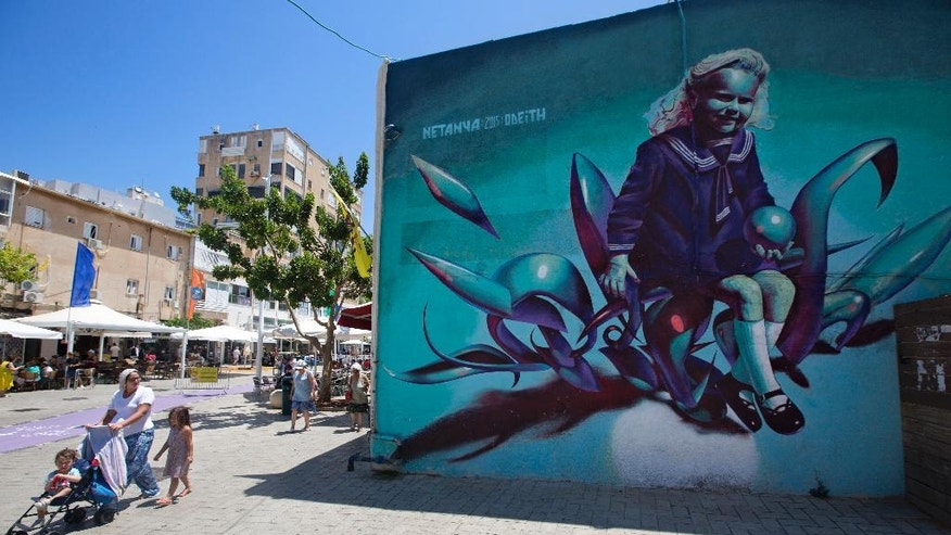 "In this photo taken Wednesday, July 29, 2015, A woman pushes a stroller next to a mural in the costal city of Netanya central Israel. Netanya markets itself as the ""Israeli Riviera"" and walking along its main pedestrian boulevard, one would be hard pressed to tell it apart from its twin city of Nice. Barely a word of Hebrew is spoken as real estate ads, restaurant menus offering baguettes and brioche and cafe conversations are all in French. (AP Photo/Sebastian Scheiner)"
